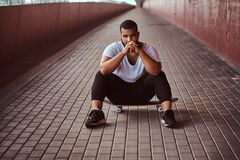Portrait of a through dark-skinned guy dressed in a white shirt and sports shorts sitting on a skateboard on a footway. Portrait of a pensive dark-skinned guy Royalty Free Stock Photos