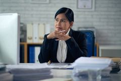 Experienced female lawyer. Portrait of pensive female lawyer at her table royalty free stock photography