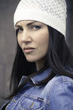 Portrait of pensive girl in jeans jacket and knitted hat Royalty Free Stock Images