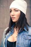 Portrait of pensive girl in jeans jacket and knitted hat Royalty Free Stock Photography