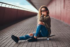 Portrait of a pensive girl in sunglasses dressed in a hoodie and ripped jeans sitting on a skateboard at bridge footway. stock photography