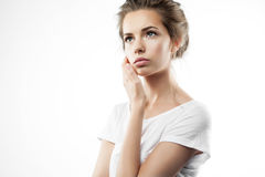 Portrait of a pensive girl in t-shirt. On gray background Royalty Free Stock Image