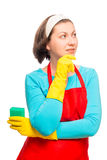 Portrait of a pensive housewife in apron with sponge Royalty Free Stock Photo