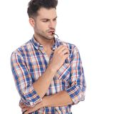 Portrait of pensive man holding sunglasses and looking to side stock photos