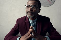 Portrait of pensive mature african american man. In eyeglasses and burgundy jacket royalty free stock photo
