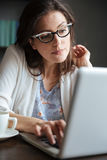 Portrait of a pensive mature business woman typing on laptop. Portrait of a thoughtful mature business woman typing on laptop while sitting at the table at home Royalty Free Stock Photos