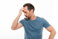 Portrait of a pensive mature man dressed in t-shirt. Looking away isolated over white background stock photography