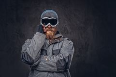 Portrait of a redhead snowboarder with a full beard in a winter hat and protective glasses dressed in a snowboarding. Portrait of a pensive redhead snowboarder royalty free stock image