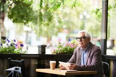 Pensive Senior Man in Cafe Outdoors. Portrait of pensive senior man sitting at cafe table outdoors holding digital tablet, copy space Stock Photos