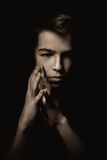 Portrait of pensive teenager on black background Stock Photo