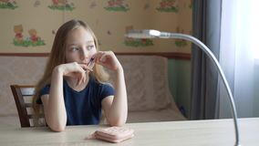 Portrait pensive teenager girl sitting at table in home office. Young school girl at work table thinking and looking to stock video