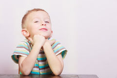 Portrait of pensive thoughtful blond boy child kid at the table Royalty Free Stock Image