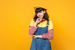 Portrait of pensive upset girl teenager in french beret, denim sundress put hand prop up on chin isolated on yellow wall. Background. People sincere emotions royalty free stock image