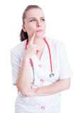 Portrait of pensive woman doctor looking up contemplative and th Royalty Free Stock Photography