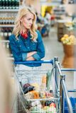 Portrait of pensive woman with shopping cart waiting for someone. In supermarket Stock Photography
