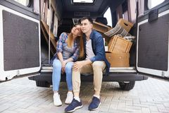 Couple Moving to New life. Portrait of pensive young couple sitting in the back of moving van resting after packing up Royalty Free Stock Image