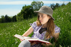 Portrait Of Pensive Young Girl With Book In Her Hands Sitting In The Grass On The Hillside And Thoughtfully Looking Sideways. Closeup Portrait Of Pensive Young Stock Photos