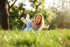 Portrait of a pensive young girl laying on a grass. At the park, reading a book, taking notes Stock Images