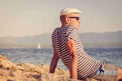 Portrait of a pensive young man with a hat sitting by the sea in summertime. Portrait of a pensive young man with a white hat sitting by the sea in summertime Stock Photos