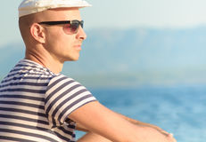 Portrait of a pensive young man with a hat sitting by the sea in summertime. Portrait of a pensive young man with a white hat sitting by the sea in summertime Stock Image