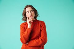 Portrait of a pensive young woman dressed in sweater. Looking away at copy space isolated over blue background Stock Images