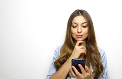 Portrait of a pensive young woman holding and looking her mobile phone with hand on her chin isolated over white background royalty free stock photos