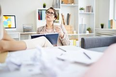Businesswoman Writing in Journal. Portrait of pensive young woman writing in notebook and looking up while daydreaming in office, copy space stock photo