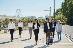 People in official clothes walking together on business trip. Portrait of people in official clothes walking together on business trip Royalty Free Stock Photo