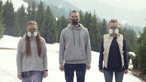 Three young men stand in gas masks bad air. Portrait of people in a respirator or gas mask in nature stock video footage