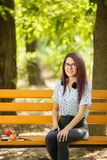 Beautiful girl sitting next to books and apple on a park background. Perfect student concept. Copy space. Portrait of a perfect student girl sitting next to Royalty Free Stock Images