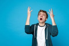 Portrait of perplexed irritated young man in casual clothes rising, spreading hands, looking up isolated on blue. Background in studio. People sincere emotions stock image