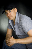 Portrait of the person in a cap. On a black background Royalty Free Stock Photos
