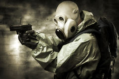 Portrait of  person in gas mask. Post apocalypses world halloween concept. Portrait of man in gas mask with handgun Royalty Free Stock Photos