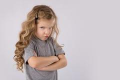 Portrait petite de la fille fâchée et triste d'isolement sur le fond blanc Photo stock