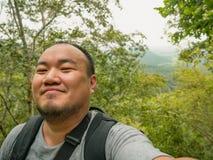 Portrait photo of Asian Tourist trekking to the top of Khao Luang mountain in Ramkhamhaeng National Park. Sukhothai province Thailand stock photos