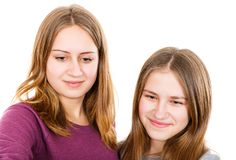 Happy young sisters. Portrait photo of happy young sisters on isolated white background Royalty Free Stock Images