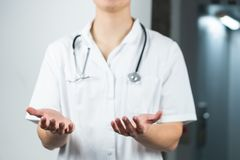 Bright close up of male doctor in uniform with stethoscope, having wide open hands. Copy space or graphic space royalty free stock photography