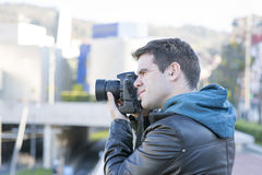 Portrait of photographer with camera  in action in the street. Royalty Free Stock Images