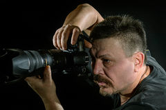 Portrait photographer with a camera on  black background. It depicts the work of photographer against a dark background Royalty Free Stock Photography