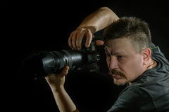 Portrait photographer with a camera on  black background. It depicts the work of photographer against a dark background Royalty Free Stock Image