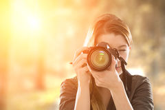 Portrait of a photographer covering her face with camera. royalty free stock photos