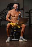 Portrait Of A Physically Fit Man Using Laptop Royalty Free Stock Image