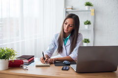 Portrait of physician doctor working in medical office workplace writing prescription sitting at desk. Stock Images