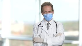 Portrait of physician in protective mask with crossed arms. Abstract blurred windows background stock footage