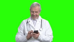 Portrait of physician typing on smart phone. Green screen hromakey background for keying stock footage