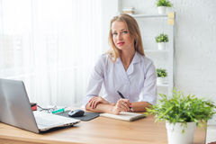 Portrait of physician working in her office. Sitting workplace Stock Photo