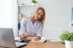 Portrait of physician working in her office. Writing prescription sitting workplace Stock Images