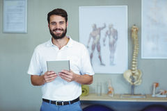 Portrait of physiotherapist holding a digital tablet. Portrait of smiling physiotherapist holding a digital tablet in clinic Royalty Free Stock Photo