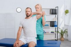 portrait of physiotherapist stretching mans arm