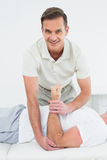Portrait of a physiotherapist stretching a mans hand Royalty Free Stock Photography